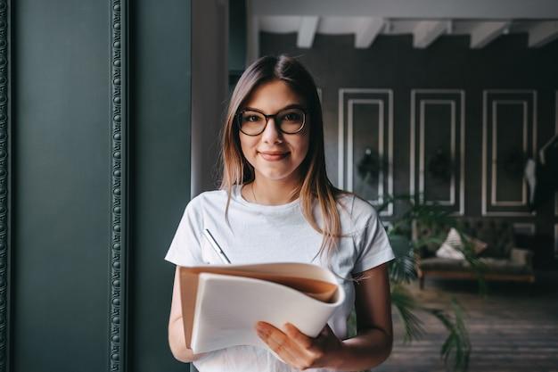 Jonge vrouw in bedrijfshal, notities maken in een notitieblok.