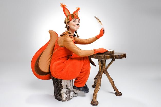 Jonge vrouw in beeld van eekhoorn die met ganzepen schrijft