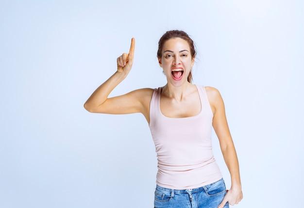 Jonge vrouw in beige atleet wijzend op iets ondersteboven