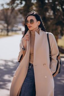 Jonge vrouw in beige jas die op straat loopt