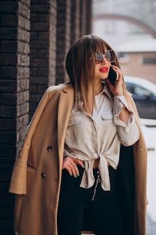 Jonge vrouw in beige jas die telefoon op straat gebruikt