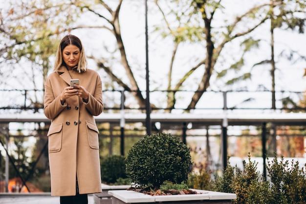 Jonge vrouw in beige jas met behulp van telefoon buiten de straat