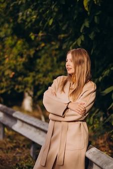 Jonge vrouw in beige jas wandelen in het park