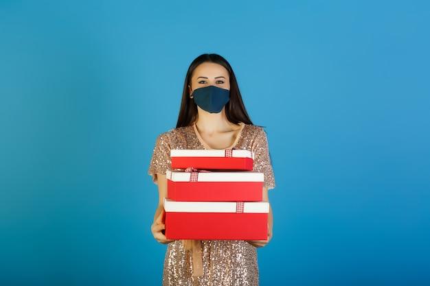 Jonge vrouw in beige jurk met pailletten in beschermend blauw masker houdt drie rood-witte geschenkdozen,