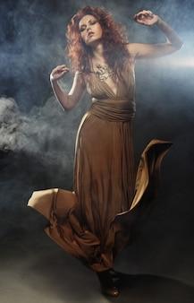 Jonge vrouw in beige lange jurk