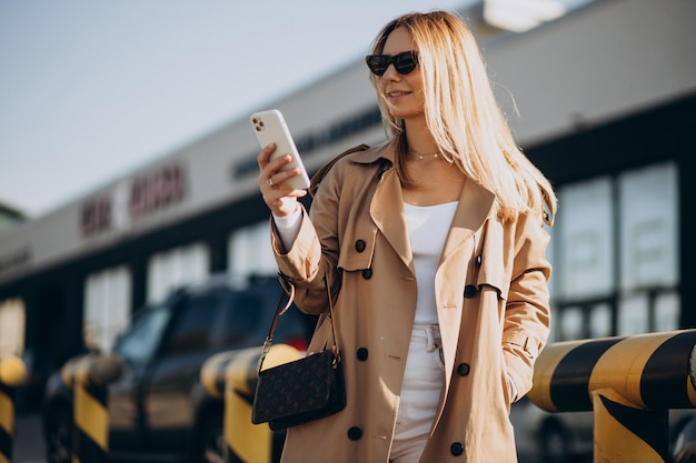 Jonge vrouw in beige loopgraaf die buiten telefoon gebruikt
