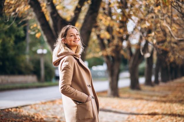 Jonge vrouw in beige pak buiten in een herfst park