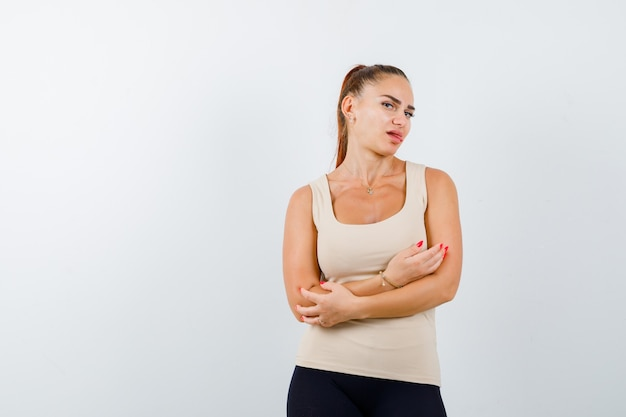 Jonge vrouw in beige tank top staande met gekruiste armen terwijl tong uitsteekt en er mooi uitziet