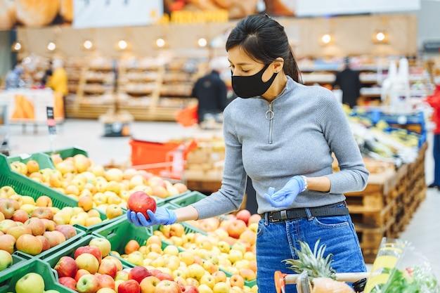 Jonge vrouw in beschermend masker en handschoenen die fruit in een supermarkt of een markt kiezen.