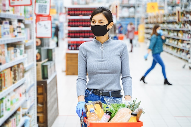 Jonge vrouw in beschermend masker en handschoenen die producten in de supermarkt kiezen. veilig winkelen tijdens een pandemie.