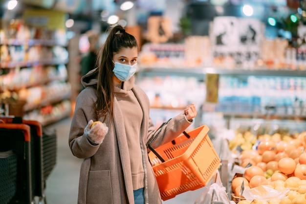 Jonge vrouw in beschermend masker maakt aankopen