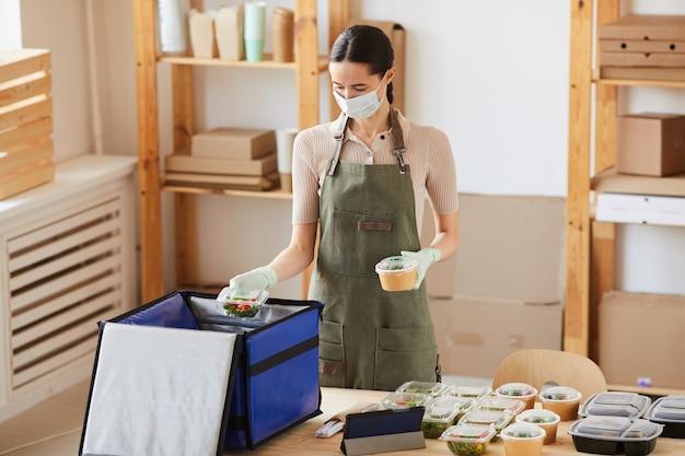 Jonge vrouw in beschermend masker voedsel inpakken in grote zak die ze werkt in de bezorgservice voor eten