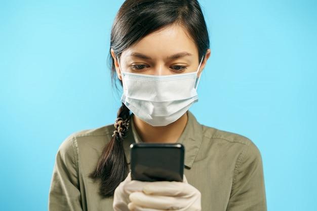 Jonge vrouw in beschermend medisch masker en handschoenen die smartphone op een blauwe achtergrond gebruiken. online chat