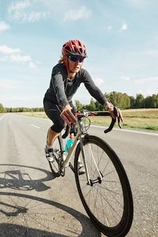 Jonge vrouw in beschermende helm rijden op een fiets op bergweg