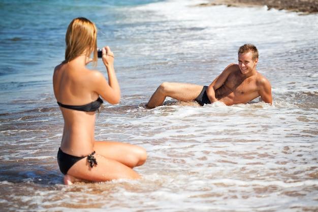 Jonge vrouw in bikini achteruit zitten en foto nemen van haar vriendje liggend in zeewater en glimlachen