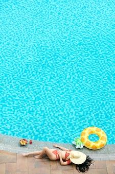 Jonge vrouw in bikini ontspannen door te zwemmen van spa hotel, ze is aan het zonnebaden naast opblaasbare ring, kom fruit en glas zoete cocktail