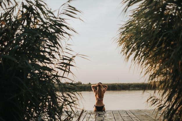 Jonge vrouw in bikini zittend op een pier aan het meer