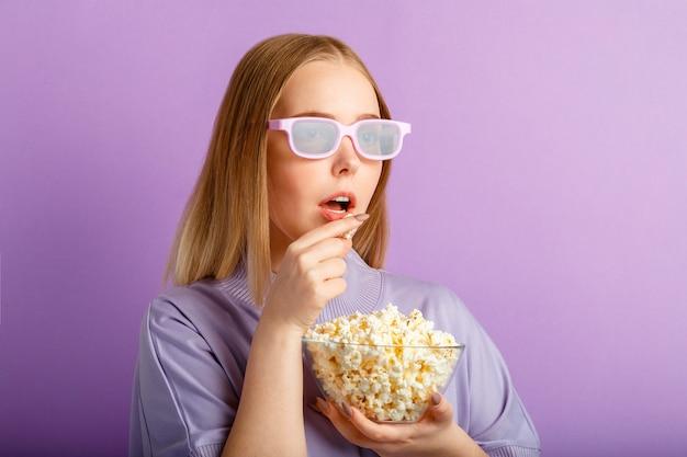 Jonge vrouw in bioscoop bril kijken naar 3d-film in de bioscoop. lachende tiener meisje film kijker in glazen eten popcorn geïsoleerd over paarse kleur muur met kopieerruimte.