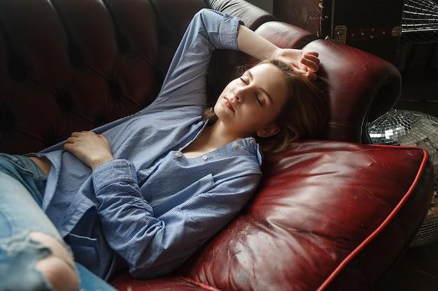 Jonge vrouw in blauw gestreept overhemd, gescheurde spijkerbroek. portret van slapend model. ligt thuis op de bank, slaapt.