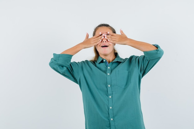 Jonge vrouw in blauw overhemd dat ogen behandelt met handen en opgewekt kijkt