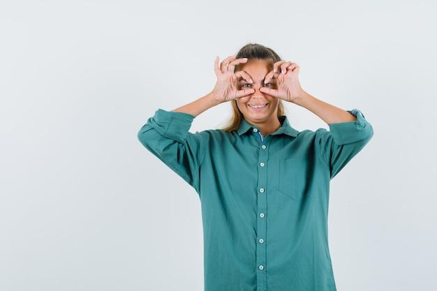 Jonge vrouw in blauw overhemd die glazengebaar tonen en grappig kijken