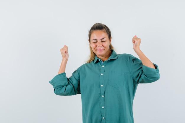 Jonge vrouw in blauw overhemd die overwinningsgebaar tonen en vrolijk kijken