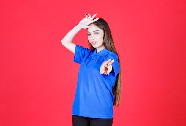 Jonge vrouw in blauw overhemd die zich op rode muur bevindt en vredesteken toont