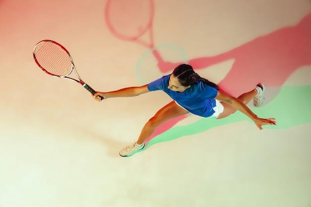 Jonge vrouw in blauw overhemd tennissen. bovenaanzicht.