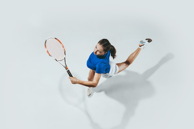 Jonge vrouw in blauw overhemd tennissen. ze slaat de bal met een racket. bovenaanzicht.