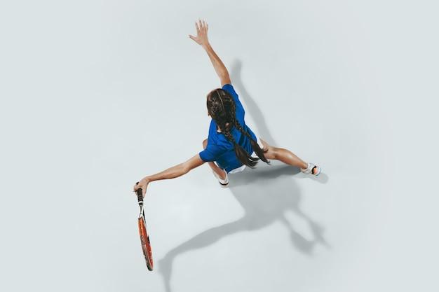 Jonge vrouw in blauw overhemd tennissen. ze slaat de bal met een racket.