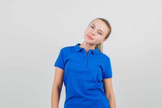 Jonge vrouw in blauw t-shirt buigend hoofd op schouder en leuk kijkt