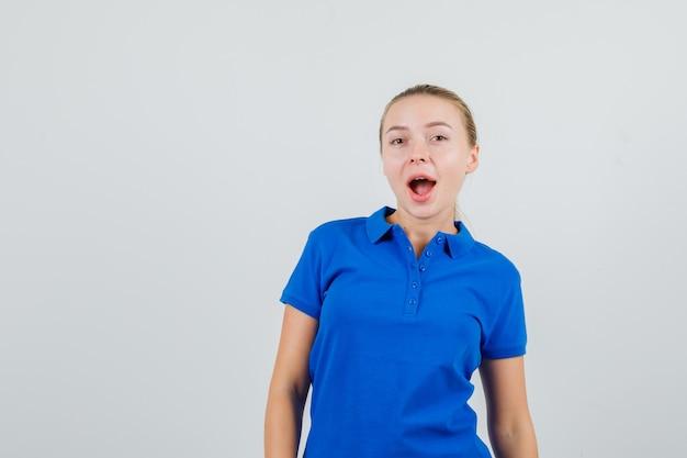 Jonge vrouw in blauw t-shirt kijkt en kijkt verbaasd