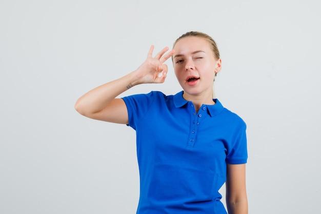 Jonge vrouw in blauw t-shirt met ok gebaar en knipogend oog