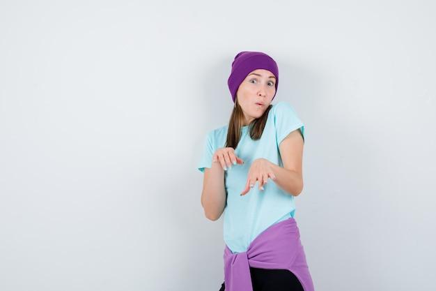 Jonge vrouw in blauw t-shirt, paarse muts die handen naar camera uitstrekt en verrast kijkt, vooraanzicht.