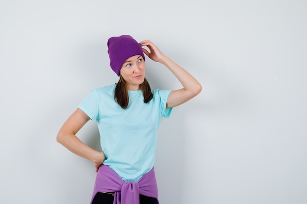 Jonge vrouw in blauw t-shirt, paarse muts die hoofd krabt, met de hand op de heup, aan iets denkt en peinzend kijkt, vooraanzicht.