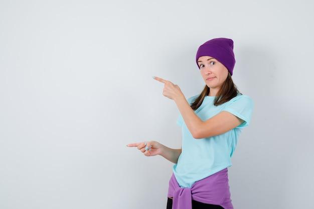 Jonge vrouw in blauw t-shirt, paarse muts die met wijsvingers naar links wijst en er gelukkig uitziet, vooraanzicht.