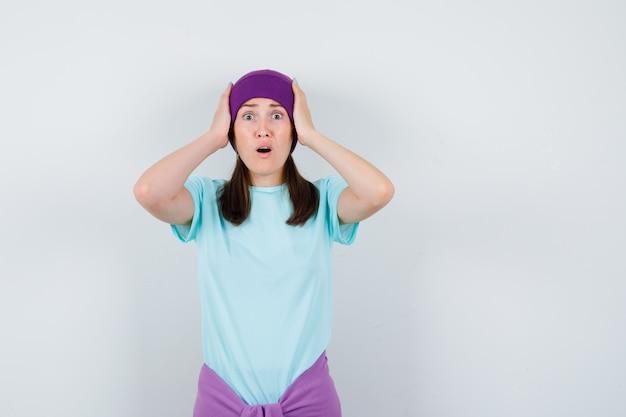 Jonge vrouw in blauw t-shirt, paarse muts met handen op het hoofd, mond open houden en geschokt kijken, vooraanzicht.