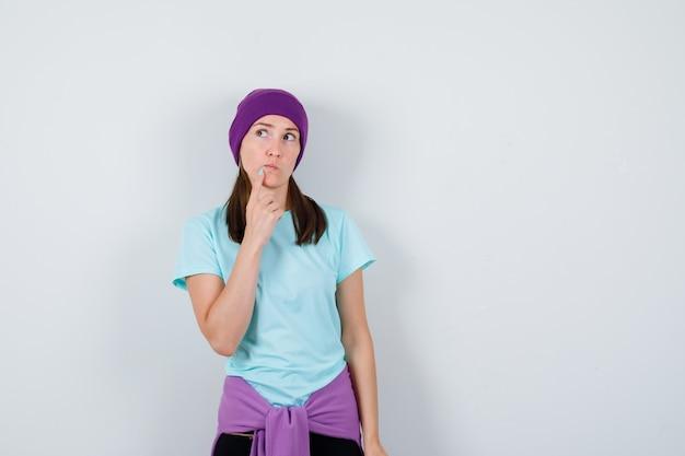 Jonge vrouw in blauw t-shirt, paarse muts met wijsvinger op kin, ergens aan denken en peinzend kijkend, vooraanzicht.