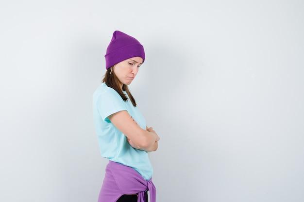 Jonge vrouw in blauw t-shirt, paarse muts staande armen gekruist, naar beneden kijkend en somber, vooraanzicht.