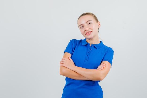 Jonge vrouw in blauw t-shirt permanent met gekruiste armen en op zoek vrolijk