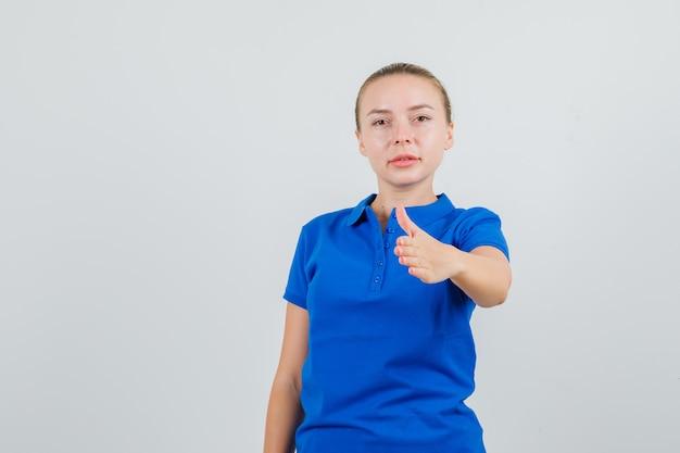 Jonge vrouw in blauw t-shirt uitrekkende hand om te schudden