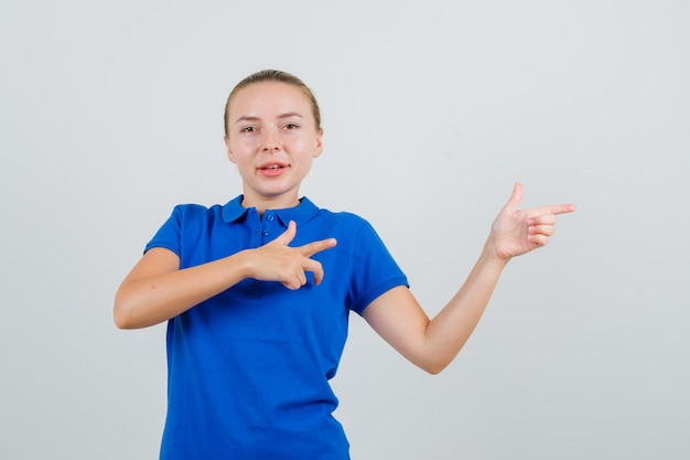 Jonge vrouw in blauw t-shirt wijst naar kant en kijkt vrolijk