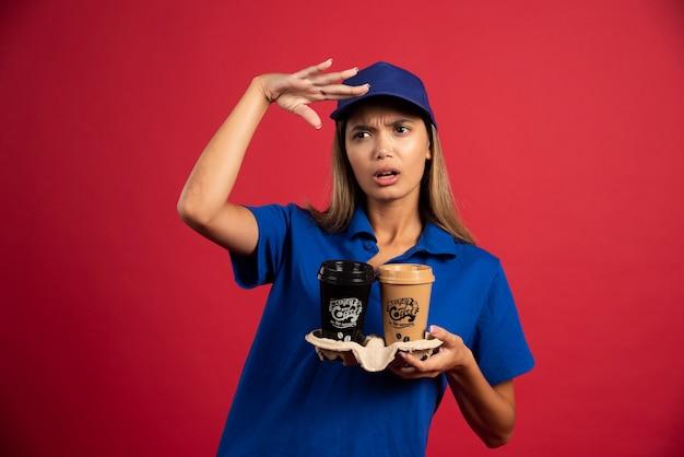 Jonge vrouw in blauw uniform met een doos met twee kopjes.