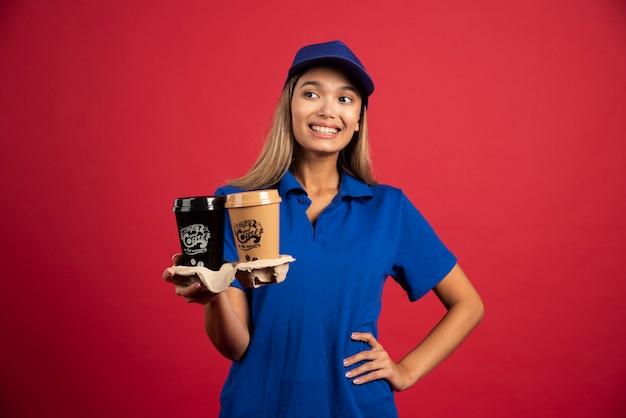 Jonge vrouw in blauw uniform met een doos van twee kopjes.
