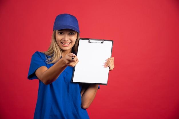 Jonge vrouw in blauw uniform met klembord wijzend op camera met potlood.