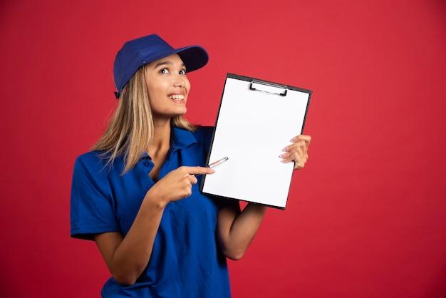 Jonge vrouw in blauw uniform wijzend op klembord met potlood.