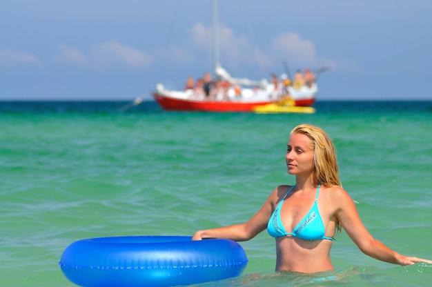 Jonge vrouw in blauwe bikini met een zwemmende cirkel