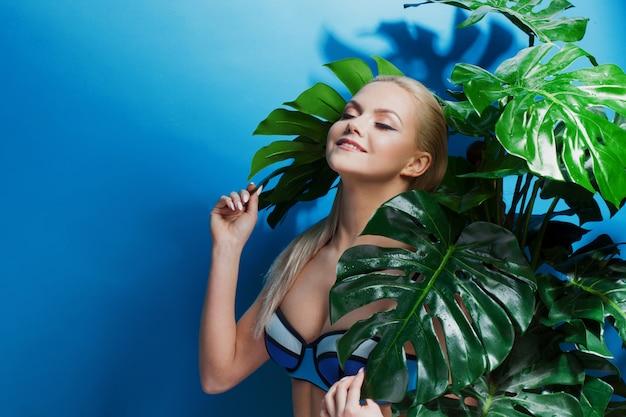 Jonge vrouw in blauwe bikini op blauw.