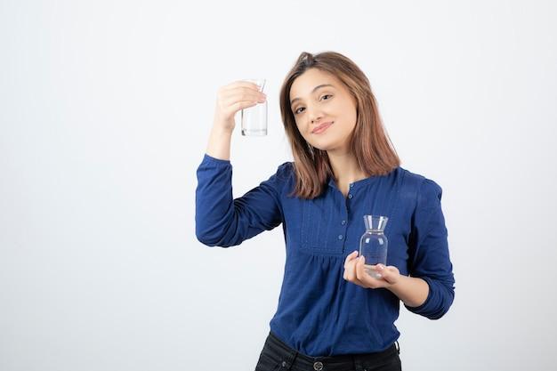 Jonge vrouw in blauwe blouse met water in haar handen.