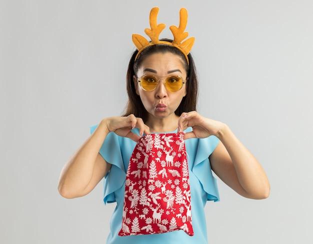 Jonge vrouw in blauwe bovenkant die grappige rand met herten hoorns en gele glazen draagt die kerstmis rode zak houden die het opent op zoek geïntrigeerd